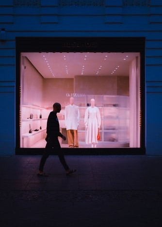 Two mannequins look out of a lighted shop window; outside on the dark street, a figure walks past, silhouetted against the window.