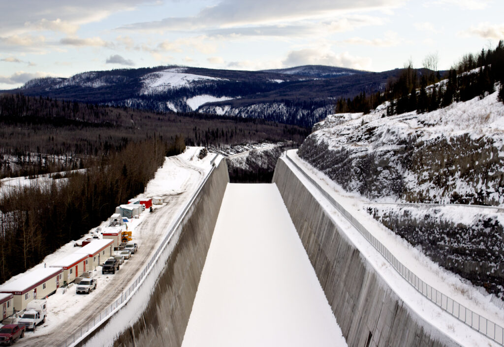 Snowy, mountainous landscape with a large concrete channel in the foreground. Caravans and cars on the left-hand wall of the channel; to the right the rising slope of a hill.