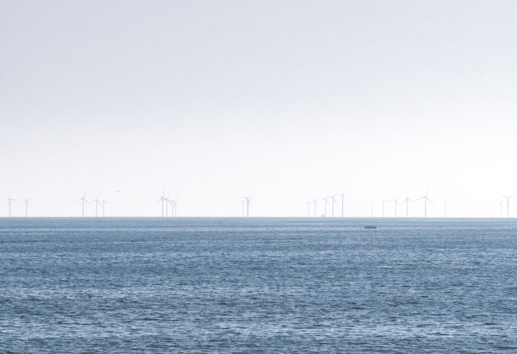 Sea and sky, with windmills visible along the skyline.