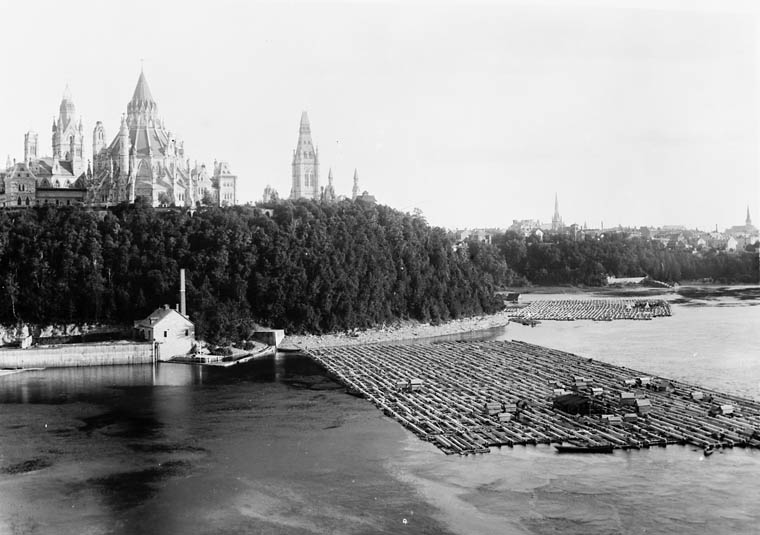 Black and white photograph of nineteenth-century Ottawa. The foreground shows a landing point with timber rafts; grand parliamentary buildings are in the background, a belt of dark trees separates the water from the buildings.