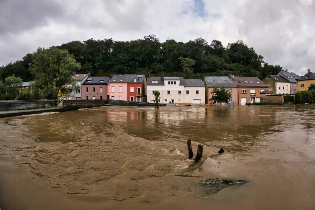 Brown floodwaters with terraced housing in the background