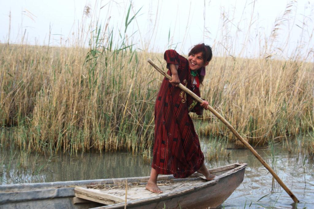 A girl punts a wooden boat through marshlands.